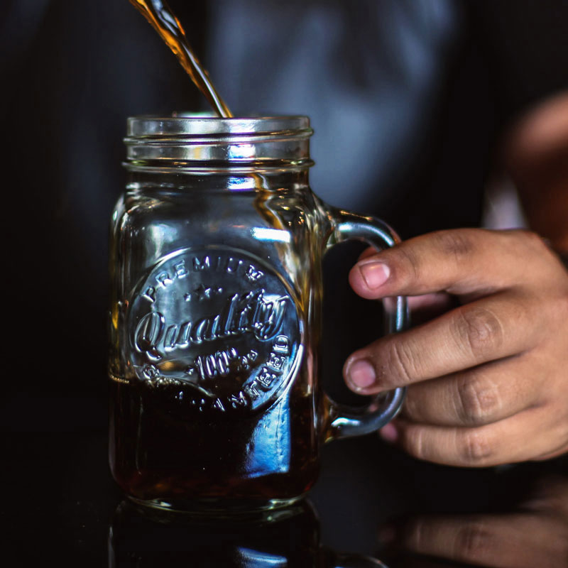 Pusser's rum being poured into a glass jar of grog